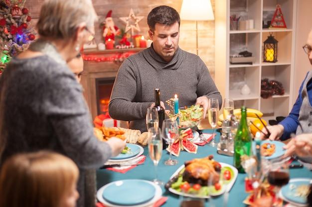 幸せな父はクリスマスの家族の夕食で彼の皿にいくつかのサラダを入れています。