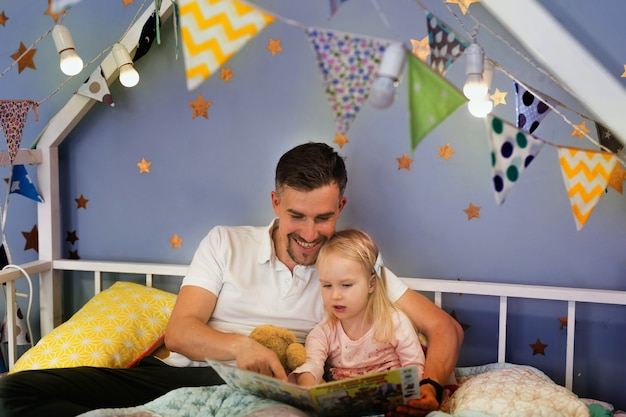Happy father reading book with his little girl while sitting on bed before bedtime together