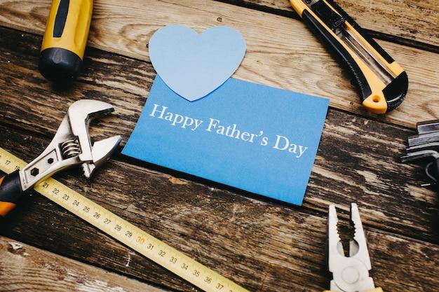 幸せな父の日の背景の概念。木製の背景に建設便利なツールの上面図。