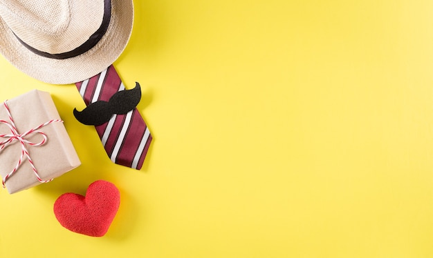 Счастливый день отца фон концепция с галстуком и усами, шляпа, подарочная коробка, красное сердце на пастельно-желтом фоне.