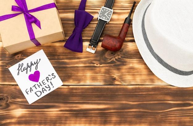 선물 상자, 상자 넥타이, 손목 시계, 모자와 나무 배경에 파이프와 함께 해피 아버지의 날 카드