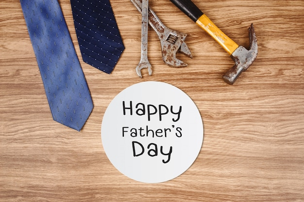 Happy father's day card with old rusty tools and tie on wooden background
