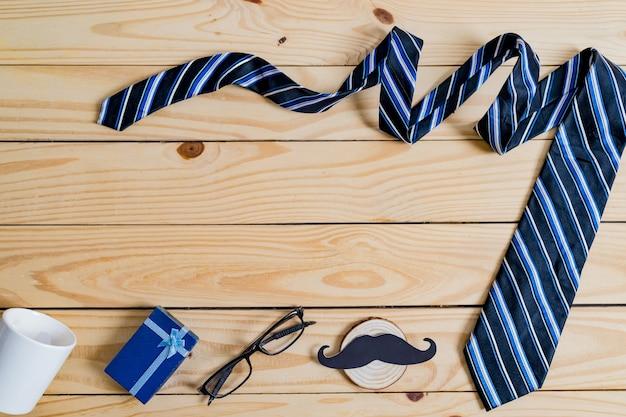 Счастливый день отца концепции. бумага с черными усами, синий галстук, синяя подарочная коробка и очки на деревянном столе.