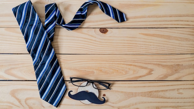 Happy father's day concept. a black mustache paper, a blue necktie and glasses on wooden table.