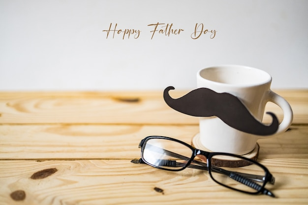 Happy father's day concept. a black mustache paper, a cup of coffee and glasses on wooden table.