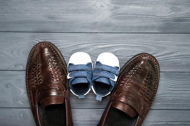 幸せな父の日のコンセプトです。お父さんと木製の背景に幼い息子の靴。テキストのための場所