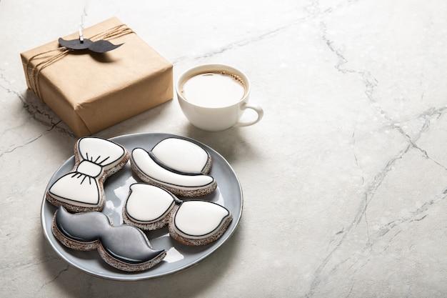 幸せな父の日のコンセプトです。おいしいクッキーと木製の背景の上にコーヒーを1杯