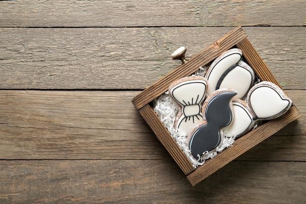 幸せな父の日のコンセプトです。木製の背景のボックスにおいしいクッキー。テキストのための場所