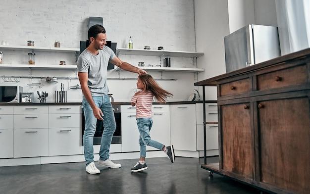 幸せな父の日。お父さんと娘が台所で踊って笑っています。