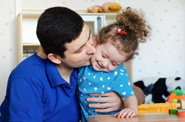 父の日おめでとう!お父さんと娘が家で楽しんで遊んでいます。親は彼の赤ちゃんにキスします。