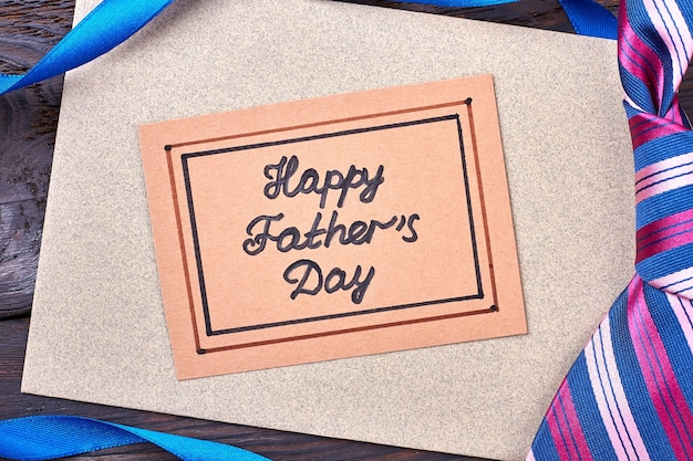 幸せな父の日のグリーティングカード。リボンと木のネクタイ。子供からお父さんまで。