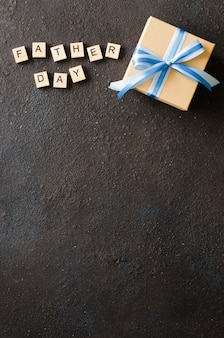 Happy father's day greeting card with decorated gift box on dark background.