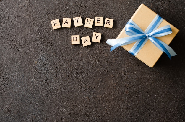 Счастливая поздравительная открытка дня отца с украшенной подарочной коробкой на темной предпосылке.