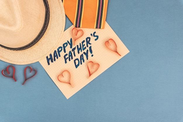 ネクタイ、帽子、青の背景にハートで幸せな父の日の碑文。ご挨拶とプレゼント
