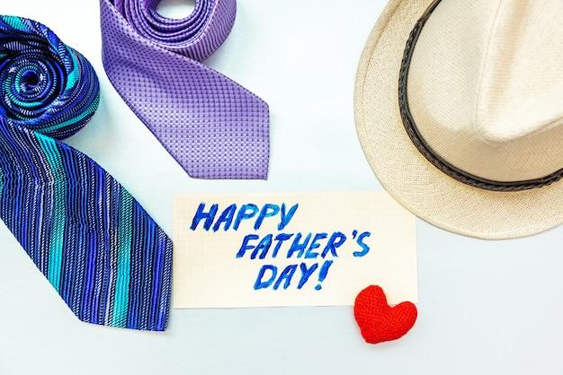 ネクタイ、ハート、白い背景の上の帽子との幸せな父の日の碑文。
