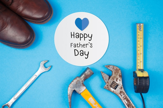 Happy father's day text on card with old rusty tools and leather shoes on blue paper background