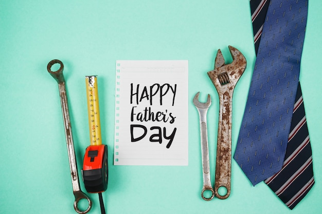 Happy father's day text with old rusty tools and ties on green paper background