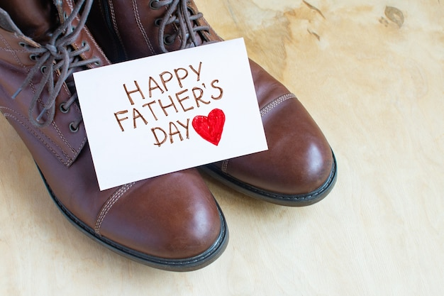 Happy father's day on a white page over brown shoes isolated on light wood background