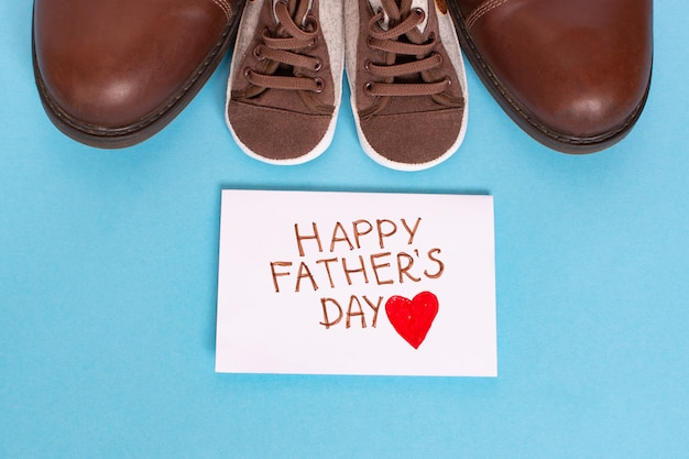 Happy father's day with red heart on a white page and kid and fathers shoes on blue background