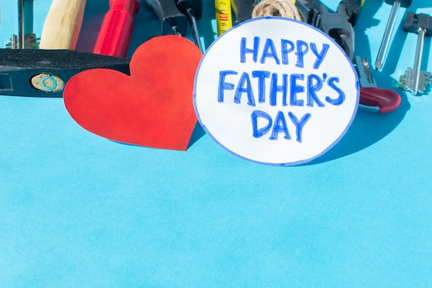 Happy father's day written on a rounded sticker with tools and a red heart on blue background