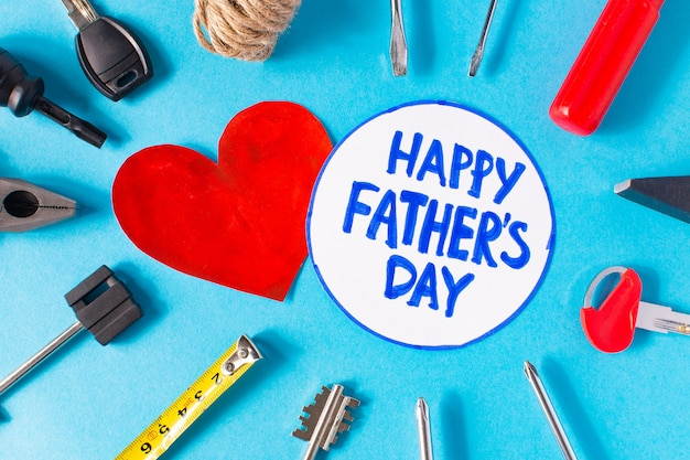 Happy father's day written with pen and a red heart with tools around on blue background