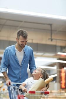 Счастливый отец, делающий покупки в супермаркете
