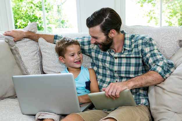 Happy father sitting by son with laptop on sofa