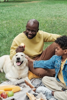 Happy father sitting on the grass with his son during a picnic, they playing with dog