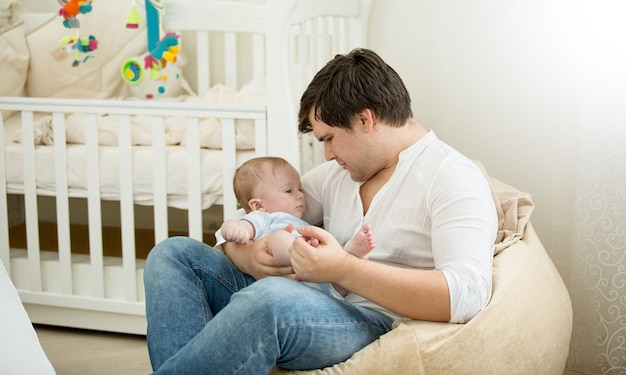 Happy father sitting with his baby son on hands at bedroom