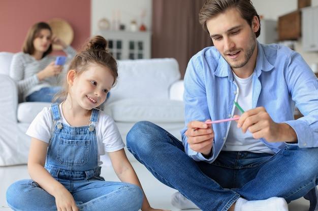 暖かい床に横たわって創造的な活動を楽しんでいる幸せな父の微笑む娘、アルバムに絵を描く鉛筆を描く、ソファで休む母、家族は一緒に自由な時間を過ごします。