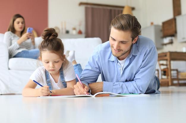Счастливый отец улыбается дочери, лежа на теплом полу, наслаждаясь творческой деятельностью, рисует карандаши, раскрашивая картинки в альбомах, мать отдыхает на диване, семья проводит свободное время вместе.