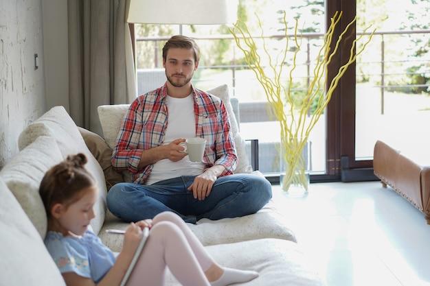 幸せな父は、創造的な活動を楽しんで、アルバムにペンの絵を描いて、ソファに座って娘を微笑んで、父と娘は一緒に自由な時間を過ごします。