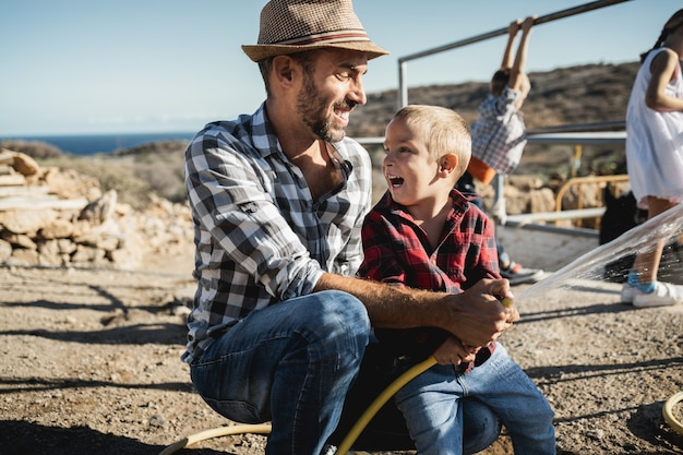 Happy father and son having fun together at ranch farm - focus on kid face