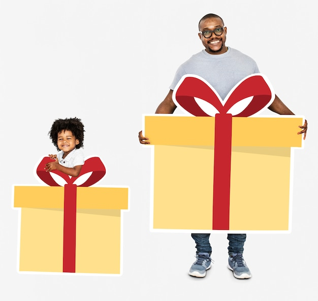 Happy father and son holding gift boxes