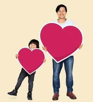 Happy father and son holding hearts