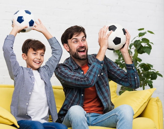 Happy father and son holding soccer balls