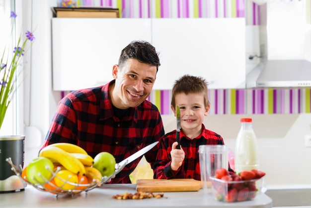 Happy father and son making healthy breakfast together. sitting in a kitchen with knife s in their hands and looking at camera.