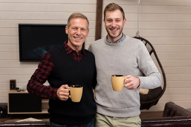 Happy father and son posing while holding cups