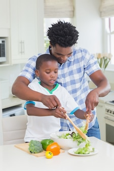 Happy father and son preparing vegetables