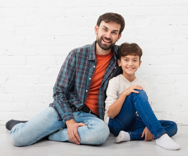 Happy father and son sitting on floor