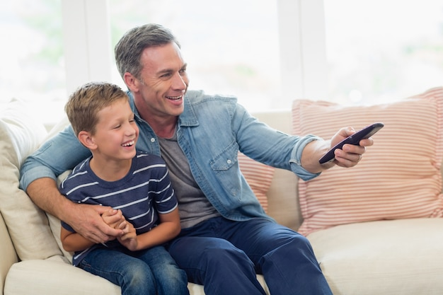 Happy father and son watching tv in living room
