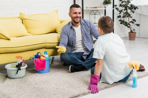 Happy father talking to son while cleaning