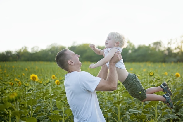 Happy father throws up his little son on sunflowers field