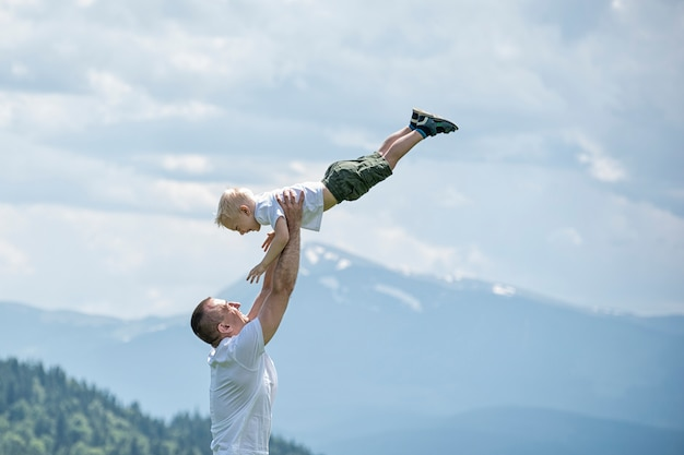 Happy father throws up a little son in green forest, mountains and sky with clouds. paternity friendship