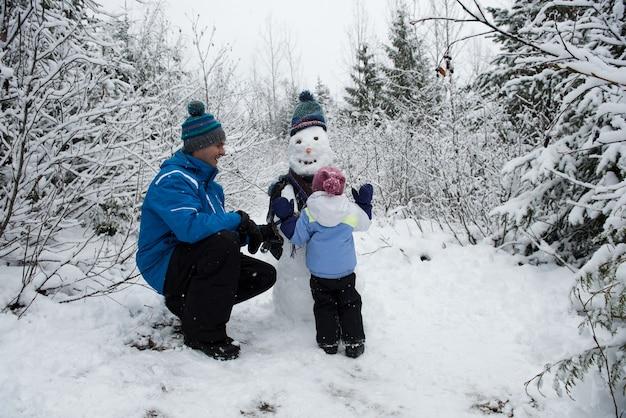 雪だるまを作る娘を見ている幸せな父
