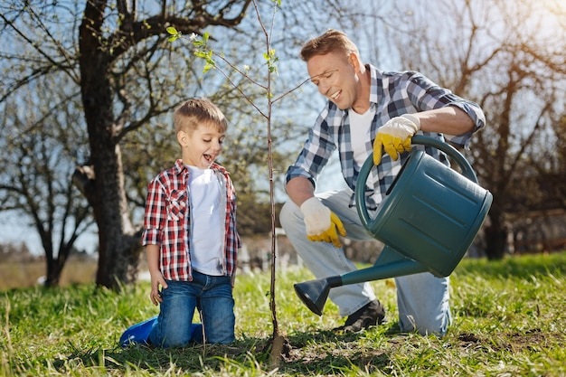 화창한 봄 날에 무릎을 꿇고 서있는 동안 사랑스러운 아들과 함께 새로 심은 나무에 물을주는 행복한 아버지