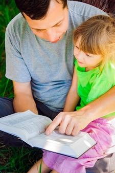 성경의 본질에 관한 책을 읽는 아이와 함께 행복한 아버지