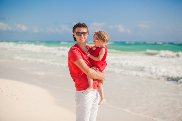 Happy father with cute daughter walking on tropical beach vacation