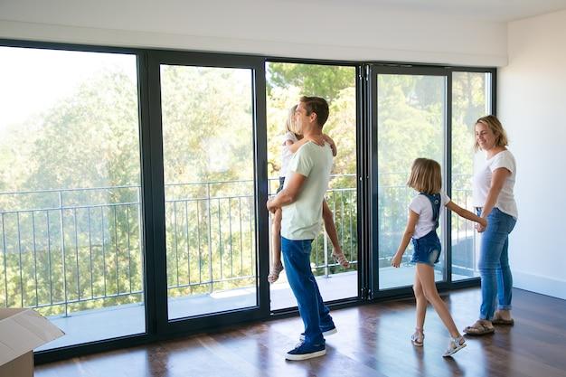 Padre felice con la figlia in piedi vicino al balcone aperto e sorridente