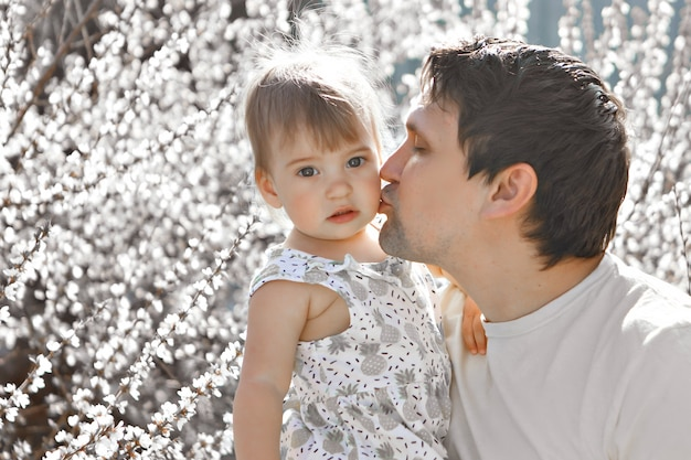 A happy father with daughter walks through a flower meadow. love and spring blooming. man and little girl. father s day